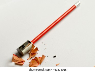 Pencil sharpener, pencil shavings and red graphite pencil, isolated on white background