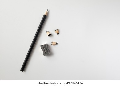 Pencil with sharpening shavings on white background