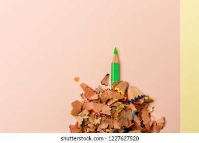 Pencil with pencil shavings on a pastel coloured background. Conceptual photo for various life situations.