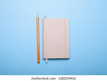 pencil and sketchbook isolated on blue background