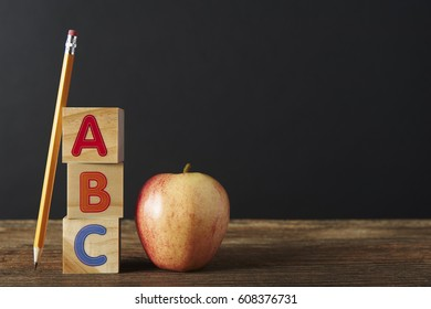 Pencil, Spelling blocks and apple on a wooden table with copy space.