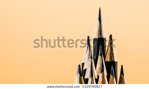 pencil standing out from crowd of plenty identical black pencils on background.business success concept.