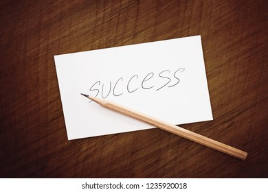 pencil and success word written on notepad