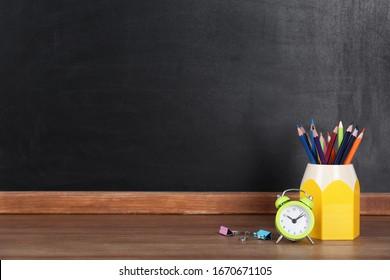 黒板の近くの木のテーブルの上の鉛筆と目覚まし時計、テキスト用のスペース。宿題をする