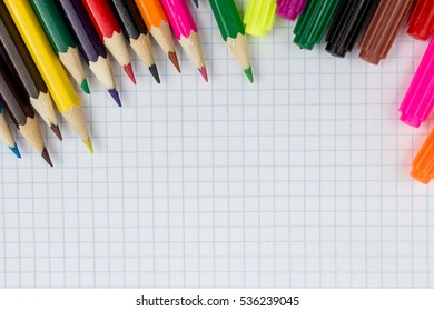 pencils and felt-tip pens on a white sheet. stationery, colored pencils and markers against each other on notebook sheet in a cage
