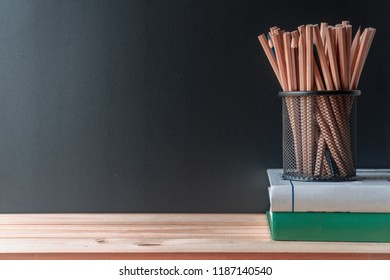Pencils in metal holder pot with books on wooden table and blackboard background