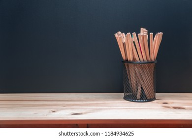 Pencils in metal holder pot on wooden table and blackboard background