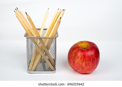 pencils in metallic box with apple on white table, office life concept