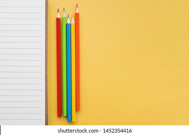 Pencils near lined paper top view