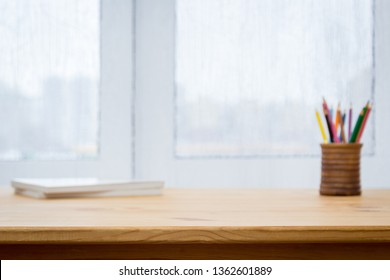 Pencils, notebooks against the background of a window, background