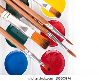 Pencils, paints and brushes on a white background