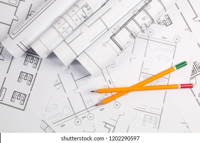 Pencils and paper engineering house drawings and blueprints.