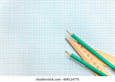 Pencils with ruller on the graph paper. Top View.