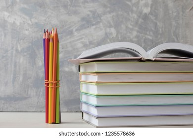 pencils and a stack of books on a white table on a concrete background