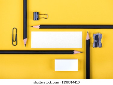 Pencils with stationery forming a rectangle over yellow background