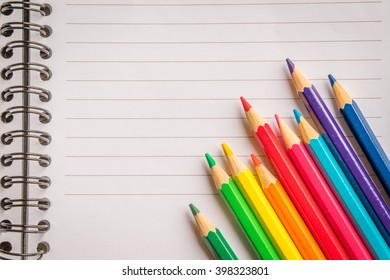 Pencils in various colors on linear paper