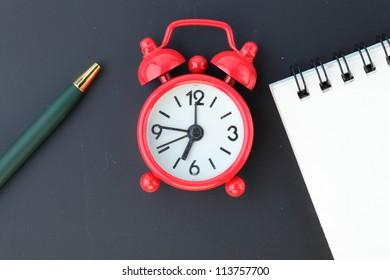 pen,clock,and notebook on blackboard