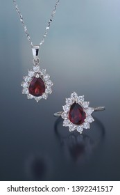 A pendant hands and ring lays on a fronted reflective surface. Both contain pear cut red garnets surrounded by white diamonds set in white gold mountings.