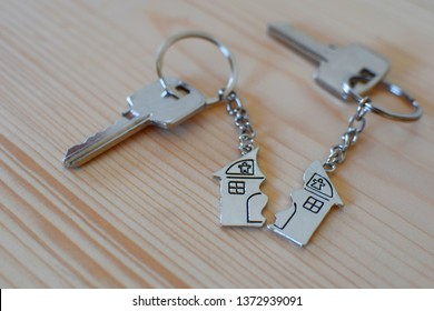 Pendant of key ring in shape of house divided in two parts on wooden background, closeup view. Dividing house when divorce, division of property and real estate.