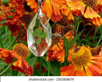 Pendant made of epoxy resin with clover on a background of flowers