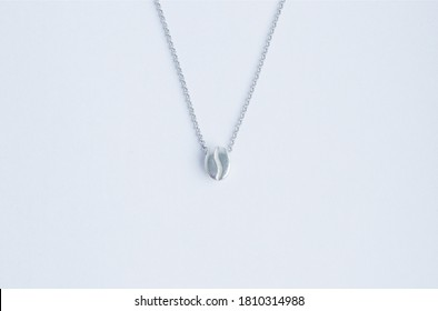 pendant made of silver in the form of a coffee zorn, on a thin chain, on a white background. Jewelry, pendant for coffee lovers. Memorable gift, relationship, love. Coffee day