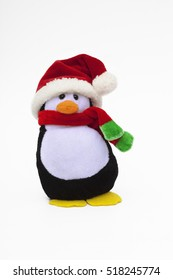 A penguin decoration dressed for Christmas with a winter scarf and Santa hat.