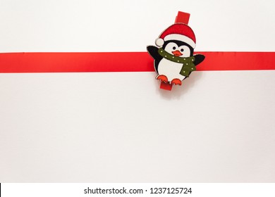 Penguin in a red hat and scarf on a white background. White background with red stripe. Background for new year greeting card. Template for post about Christmas