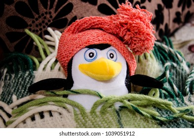 Penguin toy is ill in bed with a knitted red hat, stay in bed