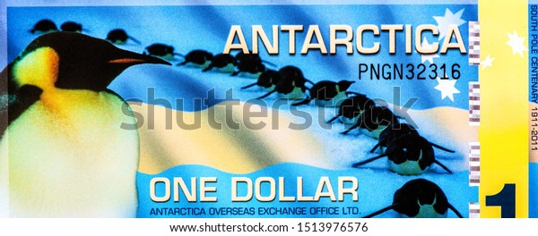 Penguins sliding down hill. Flag of Antarctica. portrait from Antarctica 1 Dollar 2011 Banknotes. Close Up Uncirculated - Collection.