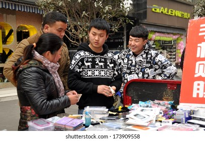 Pengzhou, China January 29, 2014: Two enterprising Chinese teenagers selling cellphone covers to married couple on a pedestrian shopping mall