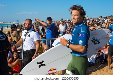 PENICHE, PORTUGAL - OCTOBER 20, 2018: Julian Wilson running to the ocean among the crowd of surf funs during the World Surf League's 2018 MEO Rip Curl Pro Portugal competition