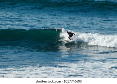 PENICHE, PORTUGAL - September 22, 2016: A recreational surfer rides a wave near Papoa Point in Peniche, Portugal.