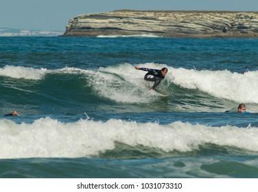 PENICHE, PORTUGAL - September 22, 2016: Recreational surfer rides a wave off Gamboa Beach in Peniche, Portugal.