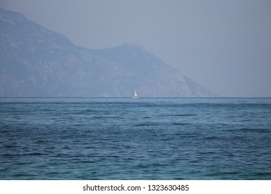 The peninsula of Athos, includes Mount Athos, with the beautiful blue sea in front. The Aegean Sea. Sailing boat in the distance