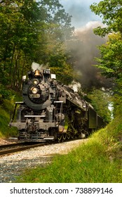 PENINSULA, OH - SEPTEMBER 17, 2917: The NKP-765, one of the largest steam locomotives still in existence, emerges from a narrow wooded pass on its annual weekend run south of Cleveland.
