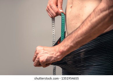 Penis size, small or large, man measuring his penis size with a measuring tape