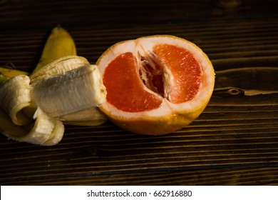 penis and vagina, banana with yellow peel in red grapefruit on wooden background, sex and sexual intercourse, fruit love, vitamin and dieting, healthy food