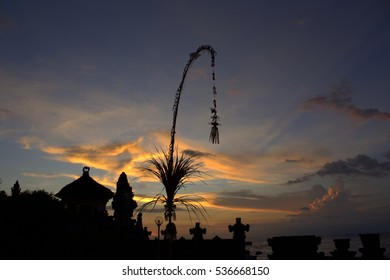 Penjor silhouette during sunset at the temple in Bali Indonesia. The penjor is a tall, curved bamboo pole decorated with coconut leaves with an offering at the base.