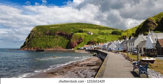 Pennan, Aberdeenshire, Scotland, UK - June 17, 2018: Row of white houses of Pennan coastal fishing village on North Sea in Aberdeenshire Scotland UK with Black Hill sea cliff