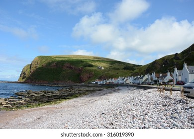 Pennan is seen nestled amongst large, imposing red sandstone cliffs.