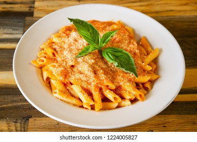 Penne alla Vodka Classic Italian Penne Vodka Dinner on a White Plate with Basil on a Wooden Table