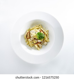 Penne Pasta Al Dente with Fried Musrooms, Parmigiano Reggiano Cheese, Spices and Basil in Plate Isolated on White Background Top View. Traditional Italian Macaroni Restaurant Serving