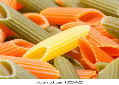 Penne pasta background. Italian colorful penne rigate pasta raw texture