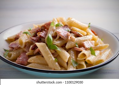 Penne pasta with bacon and sundried tomatoes. Alfredo penne pasta on white plate on wooden table. horizontal