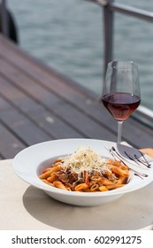 Penne pasta with bolognese sauce, parmesan cheese serve by the river with red wine