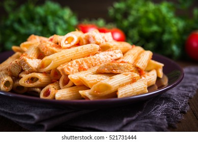 Penne pasta with chicken and tomato sauce on dark wooden background close up. Italian food. Delicious meal.
