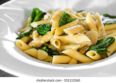 Penne pasta with a creamy sauce with parmesan cheese and basil on a white plate on a wood background isolated. Penne pasta with blue cheese sauce and spinach.