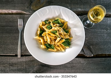 Penne pasta with a creamy sauce with parmesan cheese and basil on a white plate on a wood background isolated. Penne pasta with blue cheese sauce and spinach with vine glas and fork.