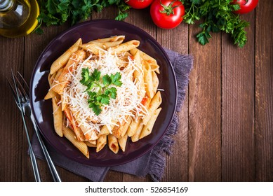 Penne pasta dish with chicken, tomato sauce, parmesan cheese and parsley on dark wooden background top view. Italian food. Delicious meal.