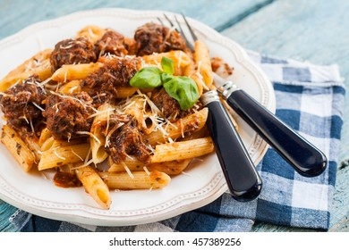 Penne pasta with meat balls in tomato sauce.